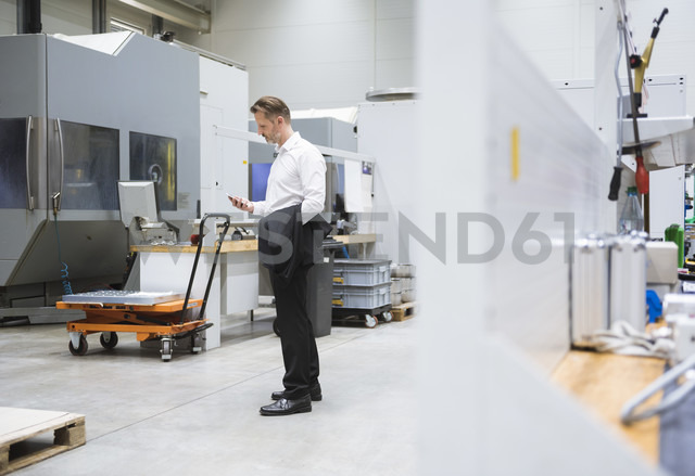 Businessman in factory shop floor looking on the phone - DIGF02032