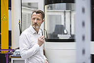 Pensive businessman in factory shop floor - DIGF02035