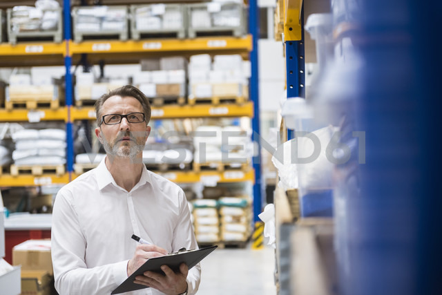 Man in storehouse taking notes - DIGF02038 - Daniel Ingold/Westend61