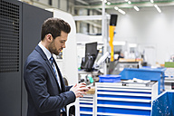 Businessman in factory shop floor using cell phone - DIGF02041