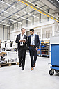 Two businessmen with tablet walking in factory shop floor - DIGF02044