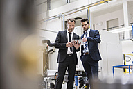Two businessmen sharing tablet in factory shop floor - DIGF02047