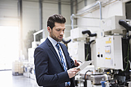 Businessman in factory shop floor using tablet - DIGF02050