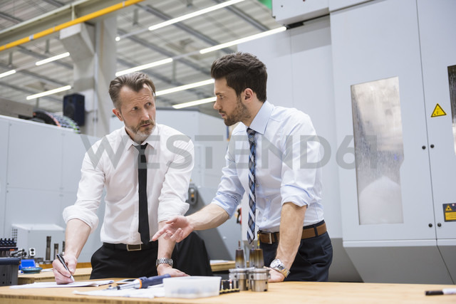 Two businessmen at table in factory shop floor discussing - DIGF02056