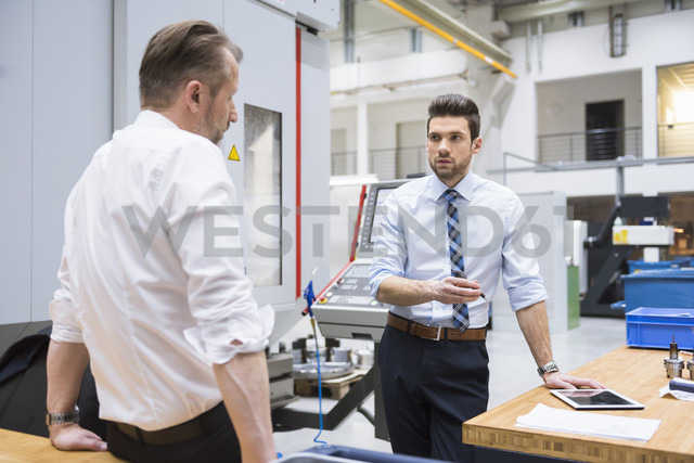 Two businessmen at table in factory shop floor discussing - DIGF02059