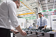 Two colleagues playing foosball in factory - DIGF02062