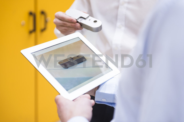 Close-up of two men with tablet and product in factory - DIGF02077 - Daniel Ingold/Westend61