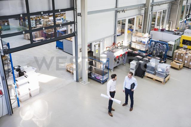 Two businessmen talking in factory shop floor - DIGF02086