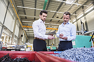 Two businessmen with tablet in factory standing at containers with shred - DIGF02089