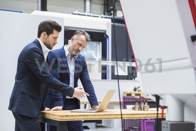Two men at table in factory using laptop - DIGF02098 - Daniel Ingold/Westend61