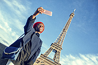 France, Paris, young woman taking selfie in front of Eiffel Tower - KIJF01384
