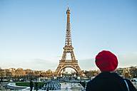 France, Paris, view to Eiffel Tower with back view of young woman standing in the foreground - KIJF01387