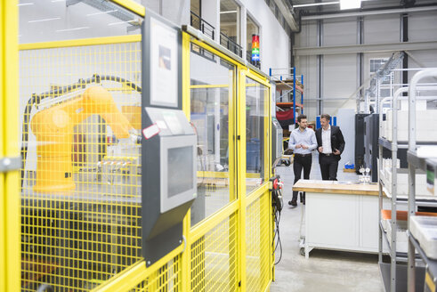Two businessman observing industrial robots in factory - DIGF02104