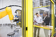 Two businessman observing industrial robots in factory - DIGF02107