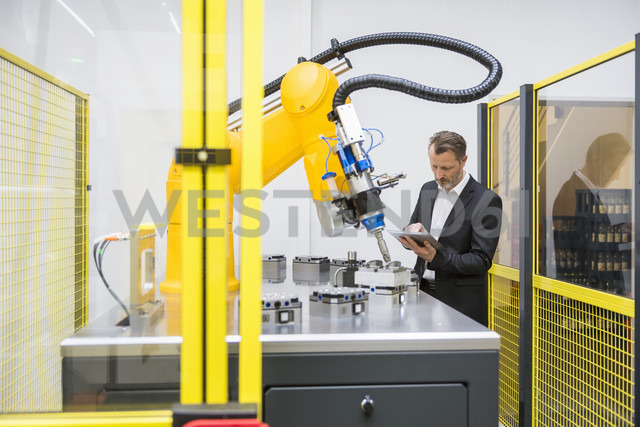 Mature businessman controlling industrial robots with digital tablet - DIGF02110 - Daniel Ingold/Westend61