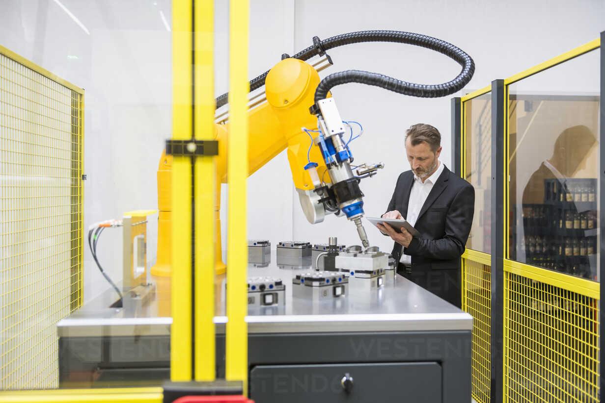 Mature businessman controlling industrial robots with digital tablet - DIGF02110 - Daniel Ingold/Westend61