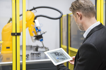 Mature businessman controlling industrial robots with digital tablet - DIGF02113