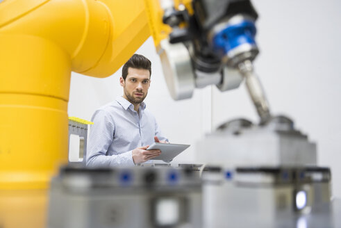 Young businessman checking automated production in factory - DIGF02116