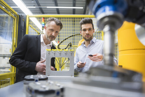 Two businessman observing industrial robots in factory - DIGF02119