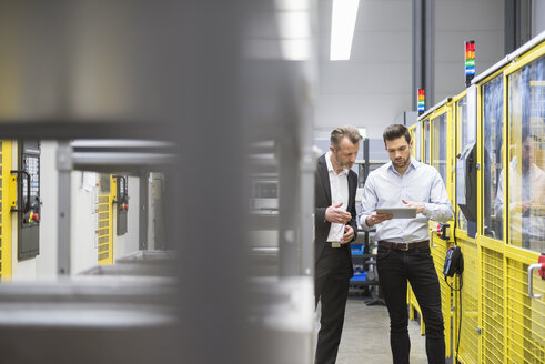 Two businessman observing industrial robots in factory - DIGF02122
