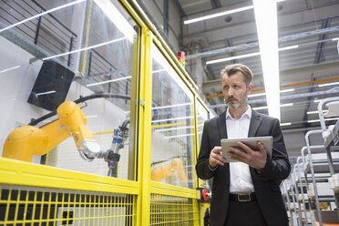 Mature businessman controlling industrial robots with digital tablet - DIGF02128