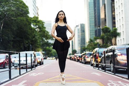 Brazil, Sao Paulo, Ballet dancer standing on tiptoes on bicycle lane - VABF01330
