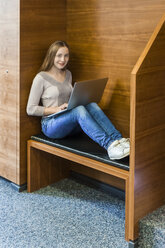 Smiling teenage girl with laptop in a public library - TCF05384