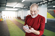 Fit senior man with smart phone in gym - HAPF01516