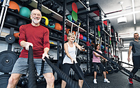 Seniors in gym working out with battle ropes - HAPF01519