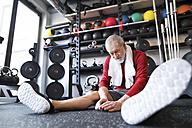 Exhausted senior man sitting on the floor after working out in gym - HAPF01528