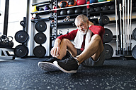 Exhausted senior man sitting on the floor after working out in gym - HAPF01531