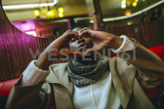 Young woman shaping hands to a heart and pouting mouth in a bar - KIJF01402