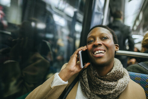 Portrait of smiling young woman on the phone in underground train - KIJF01408