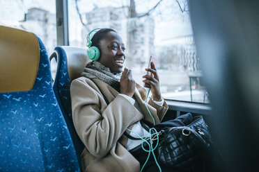 Young woman using headphones and smartphone in a bus - KIJF01414