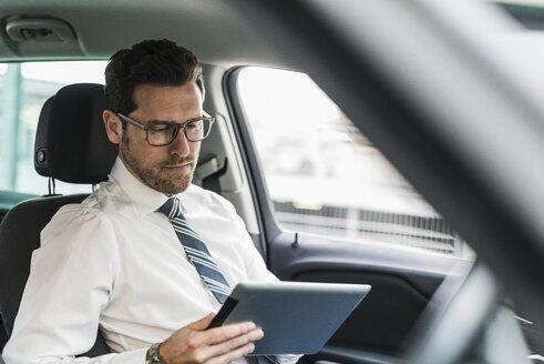 Successful businessman sitting in car using digital tablet - UUF10349