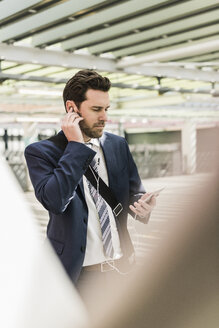 Businessman standing on parking level making a call using earphones - UUF10355