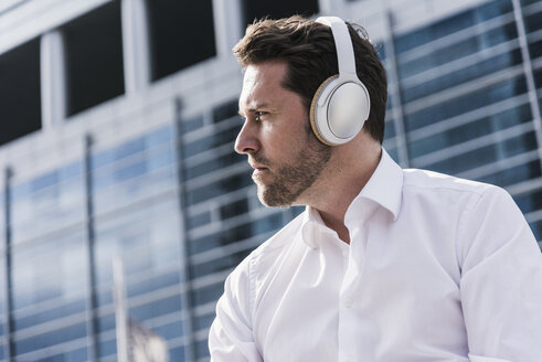 Businessman sitting in front of office building, wearing headphones - UUF10382