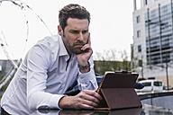 Businessman using digital tablet outdoors - UUF10385