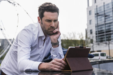 Businessman using digital tablet outdoors - UUF10385