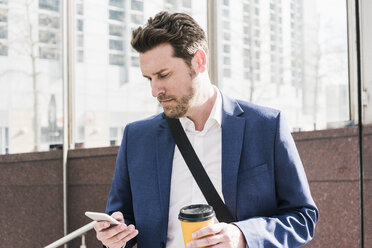 Businessman in the city, reading smart phone messages and holding cup of coffee - UUF10391