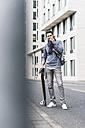 Businessman carrying skateboard, using smartphone and earphones - UUF10397