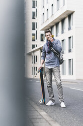 Businessman carrying skateboard, using smartphone and earphones - UUF10397