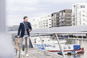 Businessman pushing bicycle in the city, while using smartphone and earphones - UUF10403