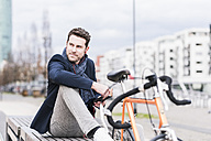 Businessman in the city with bicycle using smartphone and earphones - UUF10406