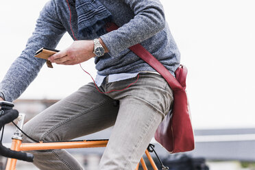 Businessman riding bicycle in the city, while using smartphone and earphones - UUF10412