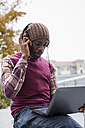 Man sitting on bench using headphones while looking at laptop - MAUF01047