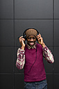 Portrait of smiling man listening music with headphones and cell phone - MAUF01062