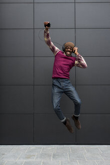 Man jumping in the air while listening music with headphones and cell phone - MAUF01065