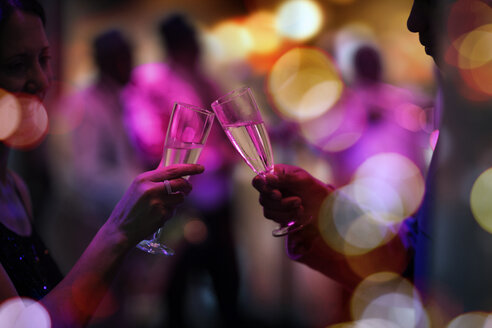 Two guests on a party clinking champagne glasses - ZEF13564
