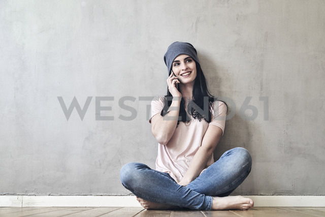 Smiling young woman sitting on the floor talking on cell phone - FMKF03992